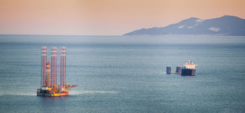 Heavy lift cargo ship and a jack up rig. A heavy lift vessel waiting for its load a jack up rig royalty free stock photography