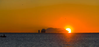 Heavy lift cargo ship. A heavy lift cargo ship and a traditional fishing boat during sunrising stock photo