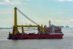 Heavy lift derrick and pipelay combination vessel. Self-propelled, dynamically positioned heavy lift derrick and pipelay combination vessel in the Strait of stock images