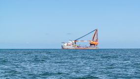 Heavy lift ship with crane sailing on North Sea leaving port of. ROTTERDAM, NETHERLANDS - AUG 28, 2015: Heavy lift ship with big ship crane sailing on North Sea stock image