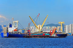 Heavy lift vessel or ship. Cargo being loaded from feeder vessels onto a heavy lift vessel docked at hong kong sea stock images