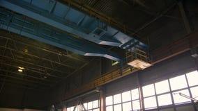 Heavy bridge crane moving alongside the factory stock video