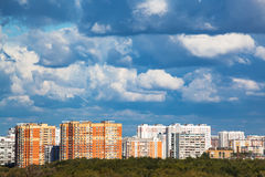 Heavy low blue clouds over modern urban houses Stock Images