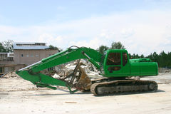 Heavy Machine Shovel - Green. Medium weight shovel in front of the buildig it's been tearing down in preparation for construction royalty free stock photography