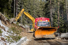 Heavy machinery building asphalt road in mountain Royalty Free Stock Photos