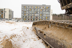 Heavy machinery caterpillar  cars houses snow Stock Photos