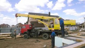 Heavy machinery and the crew of male carpenters at the construction site. Clip. Rear view of workers and machinery on