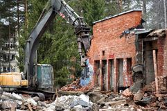 Heavy machinery demolishes a red brick building on the forest background, Visaginas city, Lithuania stock photos