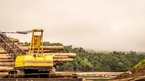 Heavy machinery loading timber into the barge. In the river. Forest exploitation, logging activity concept Royalty Free Stock Images