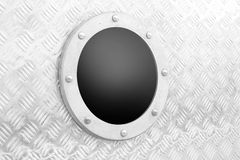 Heavy metal. Structure of a steel plate ind round window with metal frame Royalty Free Stock Image