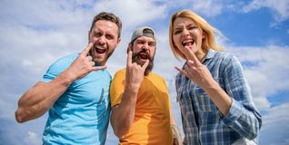 Heavy metal fans. Friends having fun summer open air festival. Men and girl enjoy music festival. Vacation and hobby. Visit famous festival during vacation stock photography