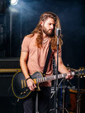 Heavy metal guitar player. Photo of a young man with long hair and beard playing electric guitar on stage Stock Photo
