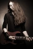 Heavy metal guitarist. Brutal heavy metal guitarist with electric guitar posing over dark background Stock Photography