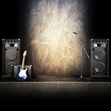 Heavy metal music stage. Or singing background, microphone, electric guitar and speakers with diamond plated flooring. Advertising concept with room for text or Stock Image
