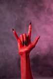 Heavy metal, red devil hand with black nails Royalty Free Stock Image