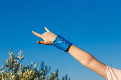 Heavy metal  and rock-n-roll sign. Female hand with blue bandana showing rock-n-roll sign on nature sky background Royalty Free Stock Photography