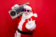 Heavy metal winter noel wish funky mood mature aged senior Nicho. Las white beard in costume headwear gloves stylish star glasses show tongue out hold vintage stock photography