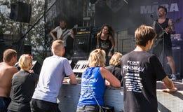 Heavy metalfans som tycker om den levande kapaciteten av lettiska rommar för  för metallmusikband MÄ royaltyfri fotografi