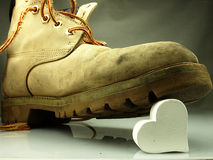 Heavy military boot trampling heart. Stock Images