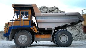Heavy mining dump trucks driving along the opencast stock video