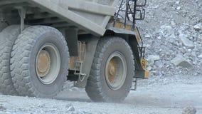 Heavy mining dump trucks moving along the opencast. Closeup stock video footage