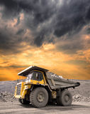 Heavy Mining Truck. Driving through the iron ore opencast on stormy sunset Royalty Free Stock Photo