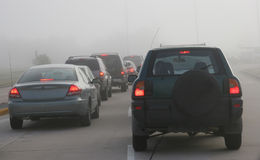 Heavy morning traffic negotiating foggy conditions. Cars in heavy traffic Stock Image