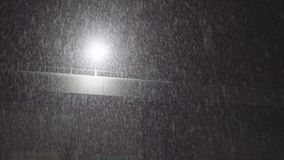 Heavy Night Snowfall with a Lamp. In the Background stock footage