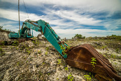 Heavy, old and broken excavator. Digger with shovel standing on hill with rocks Royalty Free Stock Photo