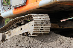 Heavy orange crawler excavator is standing on the construction site of repair and expansion  the road. Royalty Free Stock Images