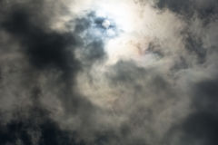 Heavy overhead dark stormy cloud formations. Sun finds gap in heavy overhead dark stormy cloud formations blowing across sky Royalty Free Stock Photography