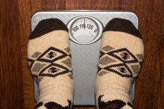 A heavy person is weighed on the floor scales. royalty free stock images