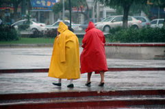 Heavy rain. Two people with rain coats in the rain Royalty Free Stock Photos