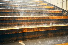 Heavy rain in the city. Rain droplets on the staircase during downpour royalty free stock photography