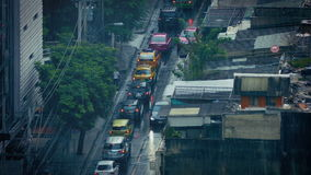 Heavy Rain On City Road In Developing Country. Urban landscape with cars and people passing in rainfall stock footage