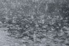 Heavy rain that crashes on the road pavement stock photography