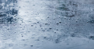Heavy rain drops on asphalt closeup. Cold toning. Heavy rain drops on asphalt closeup. Cold rainy weather concept Royalty Free Stock Images