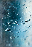 Heavy rain drops on blue window Stock Images
