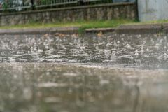 Heavy rain drops falling on city asphalt during downpour. In autumn Royalty Free Stock Photo