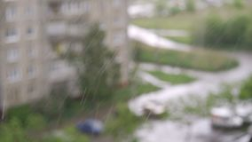 Heavy rain falling against large window pane. Raindrops trickle down, grey sky with houses outside stock video footage