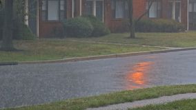 Heavy rain falling on an asphalt road in summer thunderstorm. View of street stock footage