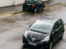 Heavy rain falling over Honda Fit car and Citroen C2. STRASBOURG, FRANCE - MAY 30, 2016: Rain drops falling over aerial view of a Honda Fit and Citroen C2 parked Stock Images