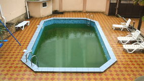 Heavy rain falls into a swimming pool. Dirty abandoned pool stock video footage
