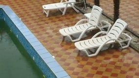 Heavy rain falls into a swimming pool. Not season, dirty abandoned pool stock video footage