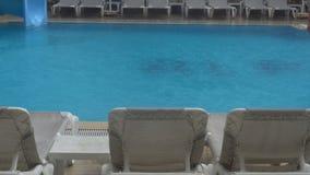 Heavy rain falls into a swimming pool. Not season, dirty abandoned pool stock footage
