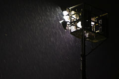 Heavy rain in night spotlight. Heavy rain at night under sportsground floodlight Royalty Free Stock Photo