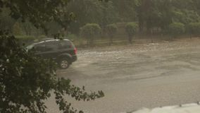 Heavy rain outside outside the window. The storm fell in the city. Cars passing through the water. The road was flooded with water stock footage