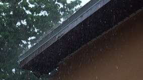 Heavy rain pouring off roof stock video footage