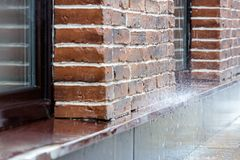 Heavy rain pouring on pavement on brick wall background Stock Photography