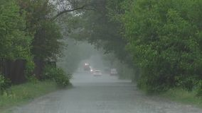 Heavy rain in spring. Heavy spring rain floods the streets with cars on the road and people passing by stock video